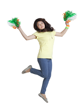 Full length portrait of young woman jumping in mid-air with Indian tricolor pom poms over white background
