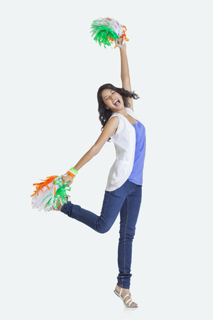Full length of young woman cheering with Indian tricolor pom poms over white background