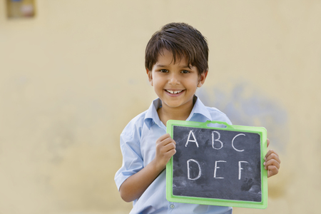 Portrait of a school boy holding slate with English alphabet on it