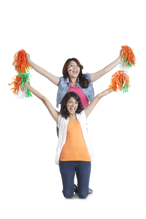 Portrait of excited young women cheering with Indian tricolor pom poms over white background