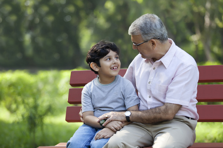 granddad: Grandfather and grandson sitting in a park Stock Photo