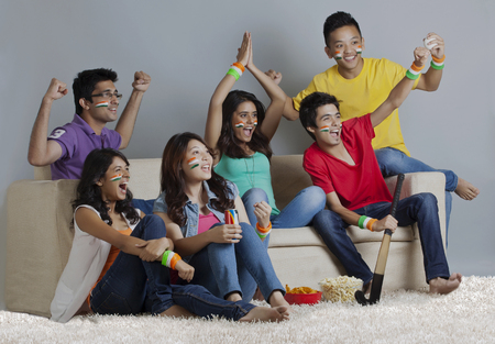 Young friends enjoying together hockey match at home Stock Photo
