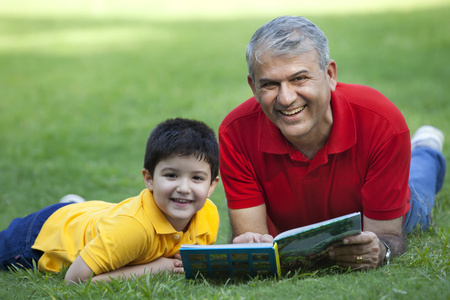 granddad: Portrait of grandfather and grandson with a book in a park Stock Photo