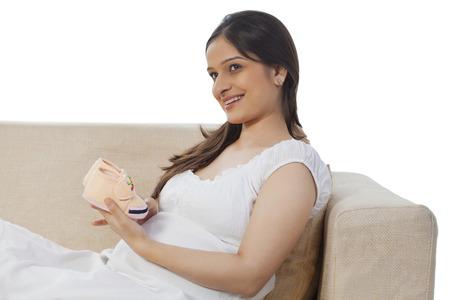 Mujer embarazada con botines de bebé