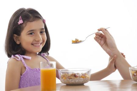 refusing: Mother feeding her daughter breakfast