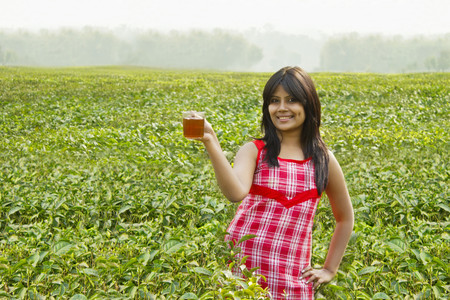 only 1 woman: Portrait of woman standing in tea plantation with a cup of tea