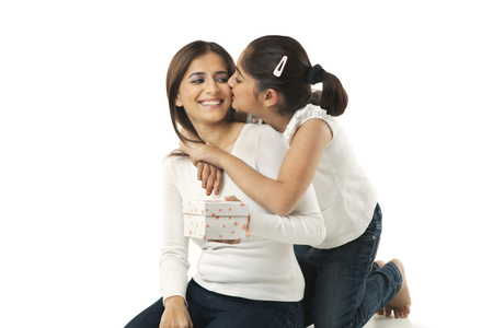Girl kissing her mother on the cheek Stock Photo