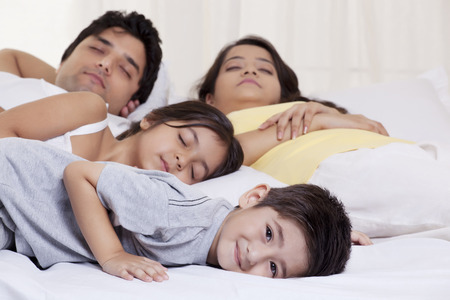 Portrait of boy smiling while his family sleeping in the background