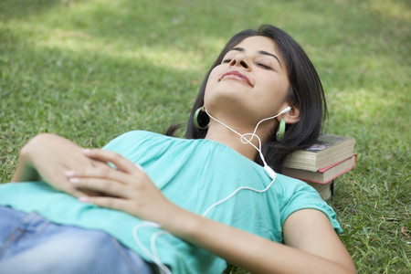 Woman lying on grass listening to music with eyes closed