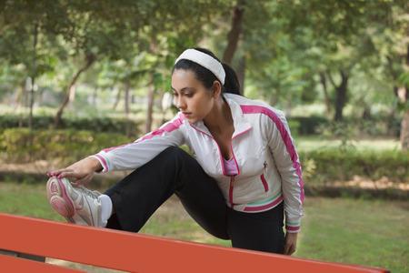 公園でストレッチ美しい若い女性