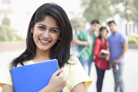 Close-up portrait of smiling young woman with friends in the background Stock Photo
