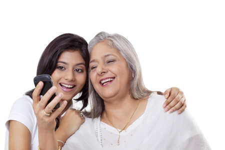 generation gap: Mature woman and her granddaughter looking at a mobile phone
