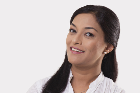 Portrait of mid adult woman smiling over white background Stock Photo