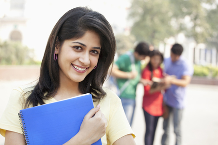 Portrait of smiling young woman with friends in the background Stock Photo