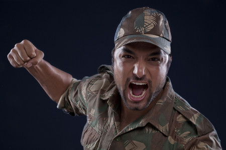 An angry young soldier shouting over black background