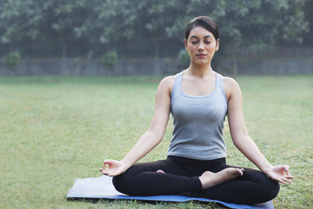Pretty young woman meditating in park Stock Photo