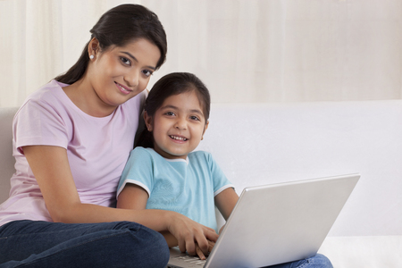 Portrait of woman helping her daughter to use a laptop
