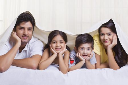 침대 덮개 아래에 누워있는 아이들과 부모님의 초상화