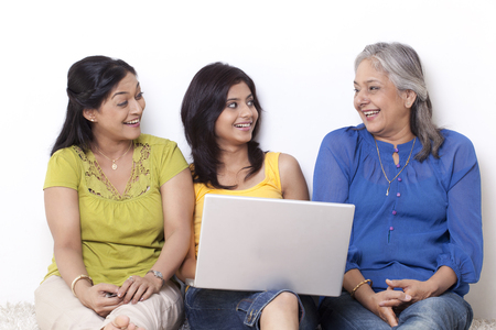 Girl sitting with her mother and grandmother shopping online