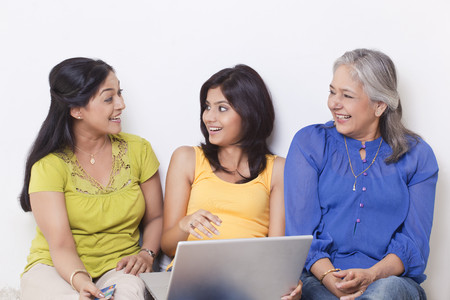 Three generational family talking while shopping online Stock Photo