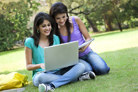 Young women taking notes from laptop