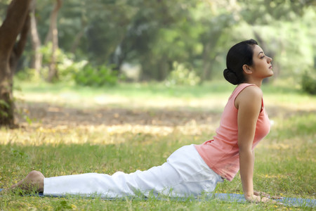 Young woman doing yoga in lawn