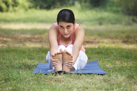 An attractive woman stretching in lawn