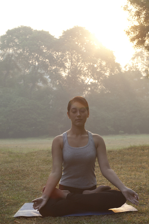 Beautiful young woman meditating in park
