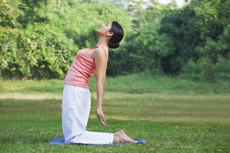 self conscious: Young woman doing yoga in park