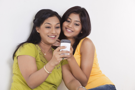 Smiling mother and daughter with cell phone