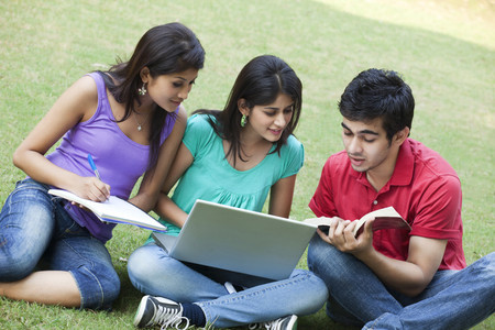 Group of students studying while sitting in lawn