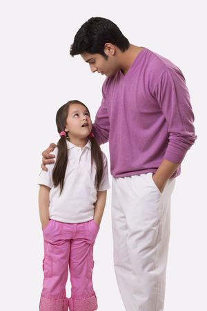 Father and daughter looking at each other over white background