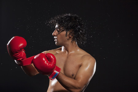 Young man tossing hair while wearing boxing gloves Stock Photo