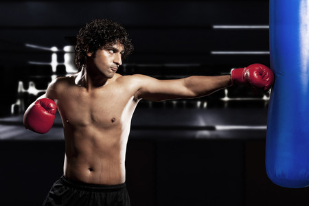 ring stand: Young man wearing boxing gloves and punching Stock Photo