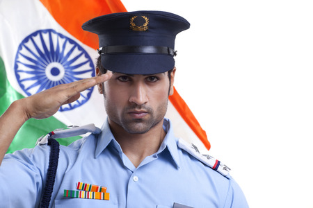 Young guard saluting with Indian flag in the background