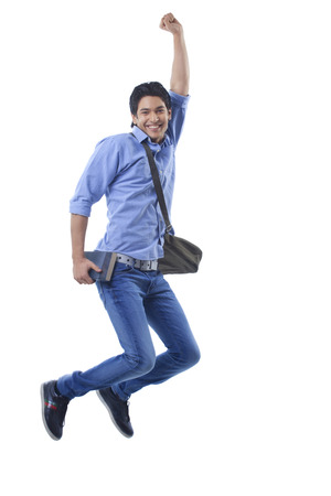 Portrait of college student jumping Stock Photo