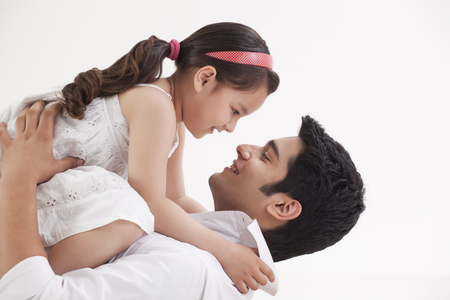 Girl sitting on fathers stomach