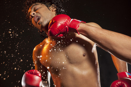 tough man: Boxer taking hit from opponent Stock Photo