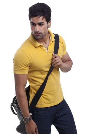 Handsome young man with duffle bag looking away