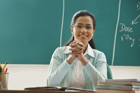 Portrait of young female teacher sitting at desk in classroom