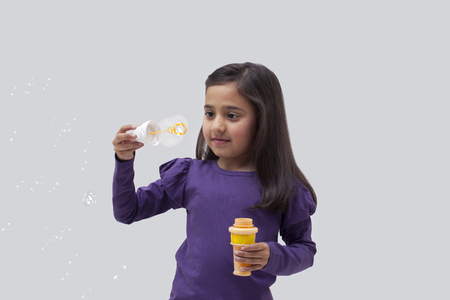 Young girl with a bubble wand Stock Photo