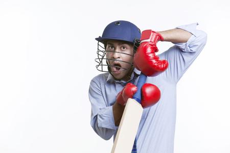 Cricketer holding bat over white background Stock Photo
