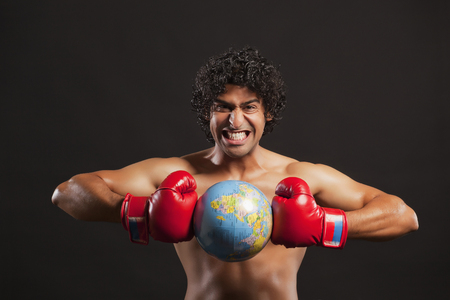 Portrait of young boxer breaking globe Stock Photo