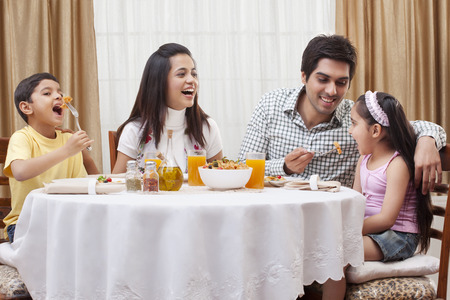 Happy parents and children eating pizza together at restaurant Stock Photo - 80371331