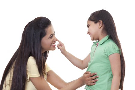 Cute little girl touching mothers nose over white background