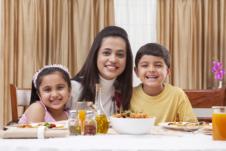 Portrait Of A Happy Mother With Her Children Having Pizza At Restaurant Photo