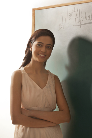 Young confident female teacher standing by green board
