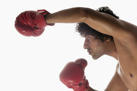 aggressiveness: Close-up of young boxer over white background