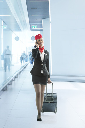 welldressed: Young air hostess pulling luggage bag while on call in the airport Stock Photo