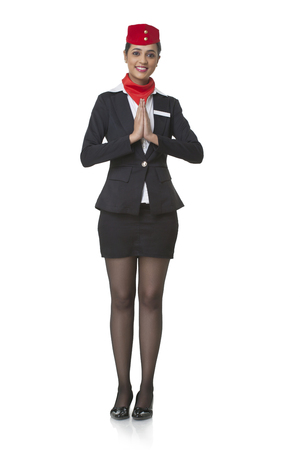 Full length portrait of young airhostess greeting Namaste isolated over white background